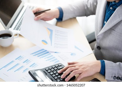 Businessman is calculating and checking the business reports from the financial imformation from business document and laptop computer. Online business and economy concept.