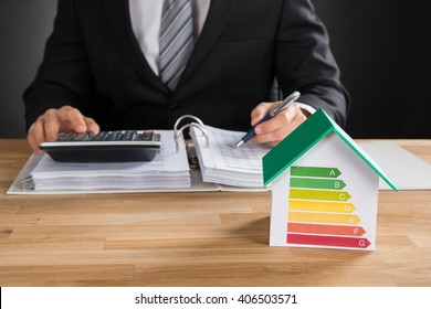 Businessman Calculating Financial Data With House Model Showing Energy Efficiency Rate On Desk