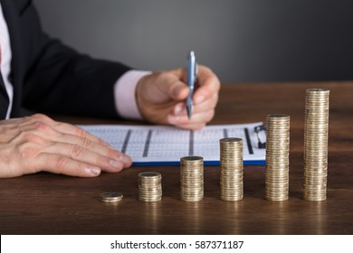 Businessman Calculating Financial Report Near Stacked Coin On Wooden Desk