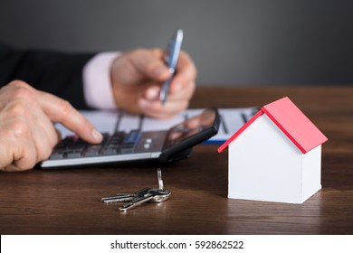 Businessman Calculating House Costs Using Calculator With House Model And Key On Wooden Desk