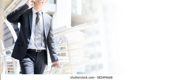 Businessman calling on cell phone while pulling baggage and walking in outdoor covered walkway, panoramic banner with copy space