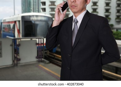Businessman calling with smart phone on blurred abstract electric train background as business, technology and communication concept.