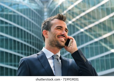 A businessman calls or writes a message or work email with the phone and smiles for the success of the employment contract and climb to success. Concept of: technology, business, success