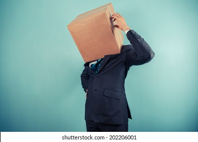 A businessman with a cardboard box on his head is scratching his head