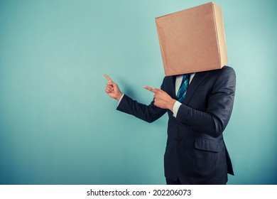 A businessman  with a cardboard box on his head is pointing