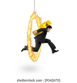 Businessman carrying 3D golden dollar sign, jumping through fire hoop, with isolated on white background.