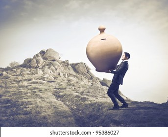 Businessman carrying a giant money box on a rock