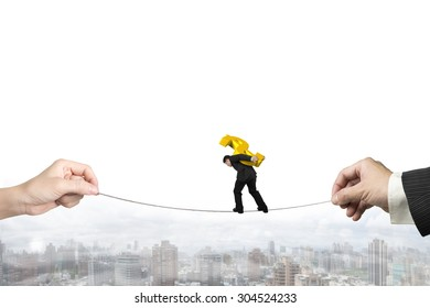Businessman carrying golden dollar sign, balancing on tightrope with man and woman hands holding two sides, on urban scene background.