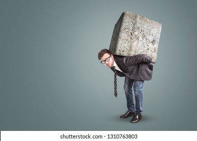 Businessman carrying a large and heavy stone on his back