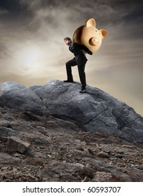 Businessman carrying a money box on his shoulders and climbing a rock