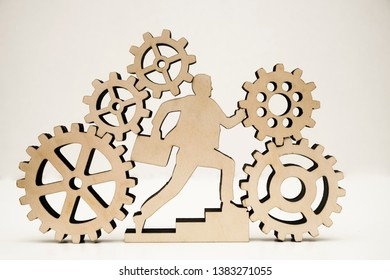 businessman with case running inside many big and small gear wheel, cogwheel isolated on white background. wooden sign, symbol of business man. missing part