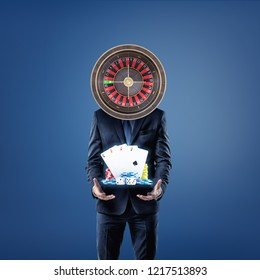 A businessman with a casino roulette instead of his head stands and offers cards, dice and casino chips. Get rich fast. Playing on market. Casino and leisure.