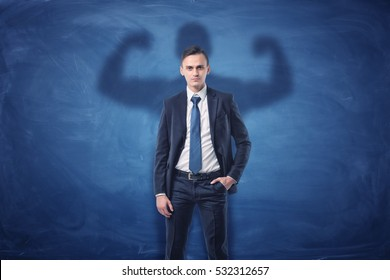Businessman is casting shadow of big strong muscular man showing his biceps. on blue chalkboard background. Inner strength. Leadership qualities. Business development.