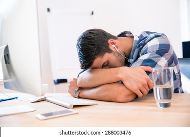 Businessman in casual cloth sleeping at the table in office