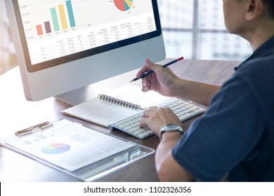Businessman in casual costume working in front of computer analysing business performance or return on investment.