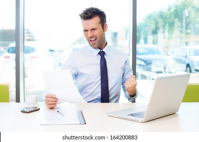 Businessman celebrate his business victory sitting at desk in the office