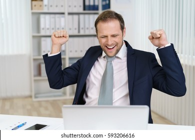 Businessman celebrating success sitting at office desk and looking at laptop screen with fists raised in yeah gesture