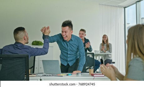 Businessman celebrating success victory looking at the laptop diverse people group clapping expressing excitement in office