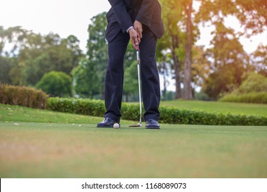 Businessman CEO Golfer hitting golf shot work out with club on course on summer vacation