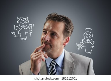 Businessman with chalk drawing angel and devil on his shoulders concept for conscience, decisions, uncertainty or moral dilemma