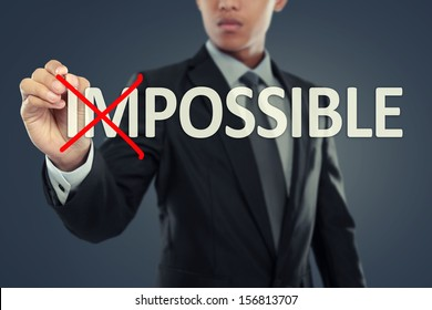 Businessman changing word impossible into possible on virtual background