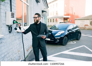 a businessman charges an electric car