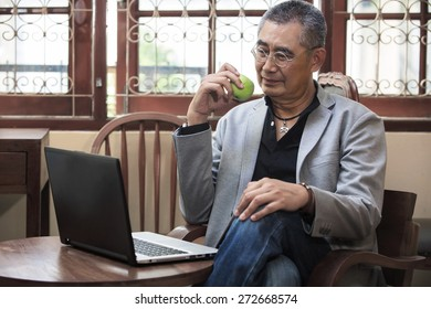 Businessman Check news and Eating A Green Apple.