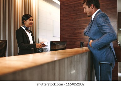 Businessman check-in at hotel reception. Female receptionist at front office talking with guest in hotel.