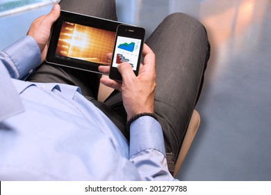 Businessman checking data on smartphone and digital tablet