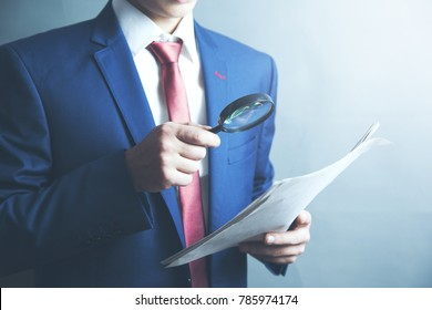 Businessman checking a document with a magnifying glass