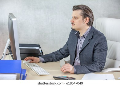 A businessman is checking the email on his computer in his office.