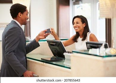 Businessman Checking In At Hotel Reception Front Desk