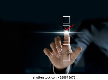 businessman checking mark on checklist with a red marker on dark background