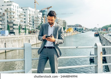 a businessman is checking is mobile phone on a bridge above a residential and industrial area