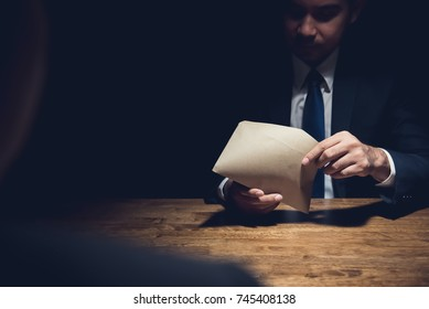 Businessman checking money in the envelope given by his partner  as a bribe in dark private room after making agreement