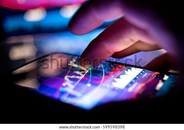 A businessman checking stock charts on a mobile device. Technology and work on the go.