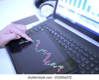 Businessman checking stock market dataมStock Market Application for Mobile, Analyzing Data Stock Market on Mobile Young Businessman with Smartphone and Stock Market Chart Background.