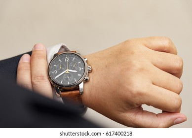 Businessman checking the time on his wrist watch, Business concept