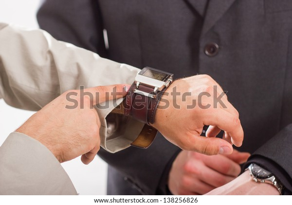 A businessman checking the time on his wrist watch.  Against the background of a man in a suit.