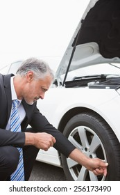 Businessman checking tire of his car