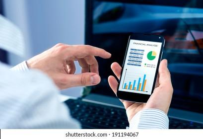 Businessman checks the financial analysis on smartphone
