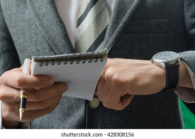 businessman checks the time on record in a notebook