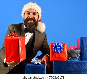 Businessman with cheerful face and stack of boxes. Christmas gift concept. Man with beard holds presents. Santa in retro suit presents blue and red gifts on blue background.