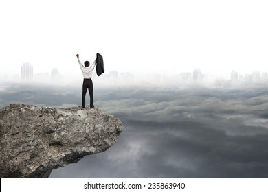 businessman cheering on cliff with gray cloudy sky cityscape background