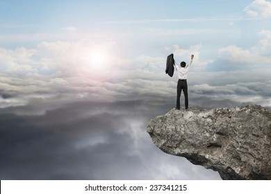 businessman cheering on cliff with natural sky daylight cloudscape background