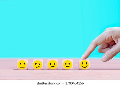 Businessman chooses a happy emoticon icons face.  Service, communication concept