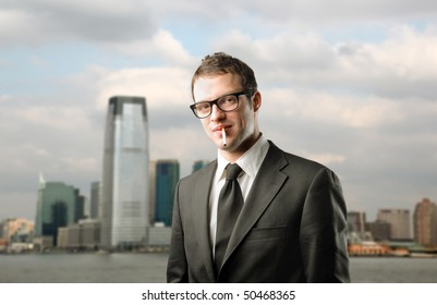Businessman with a cigarette in his mouth with cityscape on the background