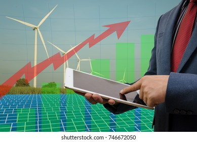 businessman and a city using a tablet solar energy Solar Energy Investment Concept.wind turbine energy concept with photovoltaic panels and wind turbines