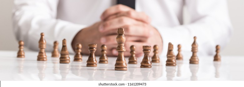 Businessman with clasped hands planning strategy with chess figures on white table.