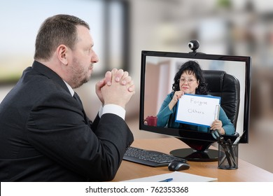 Businessman clasping his hands consults telepsychiatrist during video chat. This man in black suit suffers from depression. Patient sitting at office wooden desk looks at doctor on computer monitor